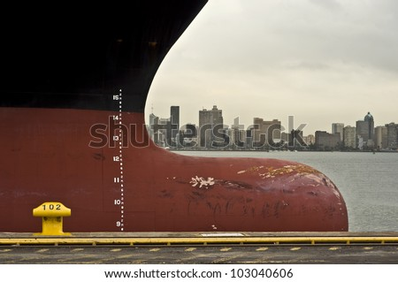 bow of large ship with draft scale numbering , large african city in the background (durban, south africa) - stock photo