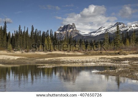 Bow River, near Banff, Alberta. With mountainous background on a cloudy morning. - stock photo