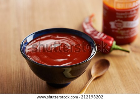 Bowl and bottle of sriracha sauce - stock photo