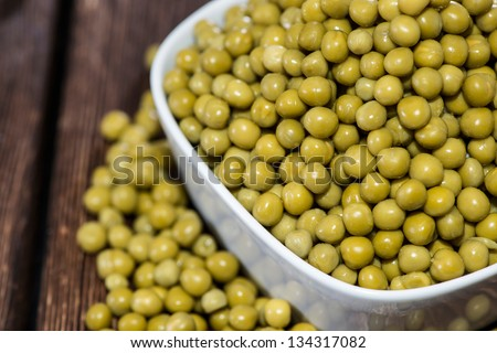 Bowl filled with canned Peas on wooden background