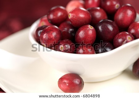 Bowl filled with cranberries on red background