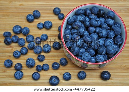 Bowl filled with fresh blueberries on old wooden cutting board