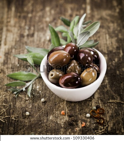 Bowl filled with freshly harvested whole fresh black olives on a rustic wooden tabletop - stock photo
