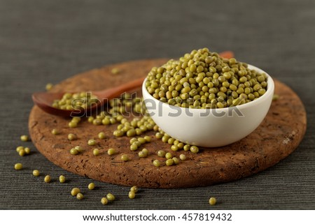 Bowl filled with mung beans on wooden background