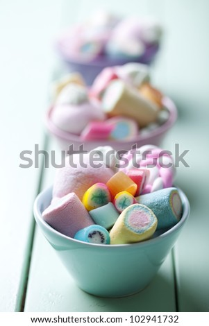 bowl full of colorful pastel marchmallows and rock candy - stock photo