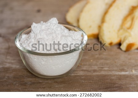 Bowl full of flour and bread on wooden background