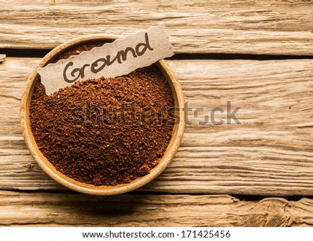 bowl full of ground coffee over an old wooden table - stock photo