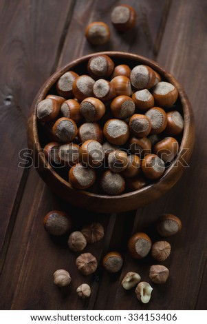 Bowl full of hazelnuts on a dark wooden surface, selective focus