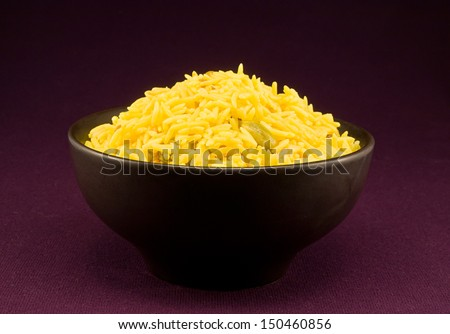 Bowl full of pilau rice a special gourmet indian side dish flavoured with spices from india including cumin, cardamom and bay leaves - stock photo