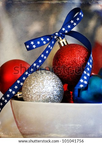 Bowl full of red white &blue Christmas ornaments with an old flag background for a patriotic Christmas theme - aged with a texture - stock photo