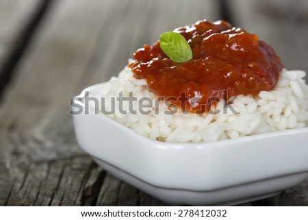 Bowl full of rice and tomato sauce over wooden background - stock photo