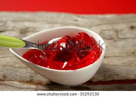 Bowl full of strawberry red sweet jelly and green spoon - stock photo