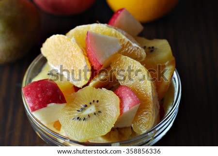 Bowl of assorted fresh fruits : Apple, oranges, kiwi and banana in a glass bowl on a wooden board. - stock photo
