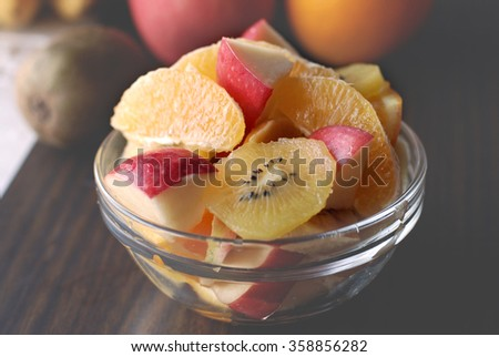 Bowl of assorted fresh fruits : Apple, oranges, kiwi and banana in a glass bowl on a wooden table. Image is treated with lightness effect for background purposes. - stock photo
