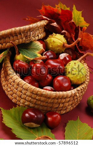 bowl of autumn chestnuts and leaves on brown background - stock photo