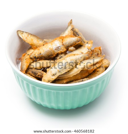 Bowl of battered whitebait sprats (Sprattus sprattus) isolated on a white studio background.