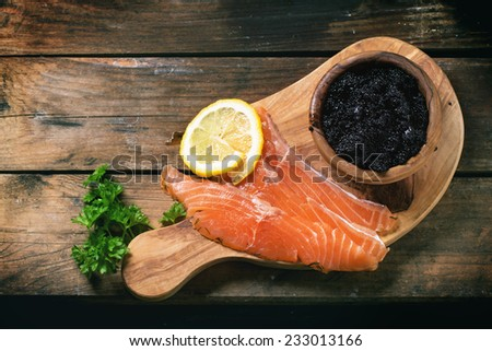 Bowl of black caviar and pieces of salted salmon on olive wood board with vintage knife over old wooden table. Top view. - stock photo