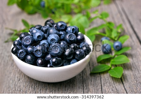 Bowl of blueberries on wooden table - stock photo