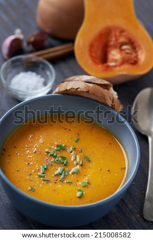 Bowl of butternut soup garnished with chives, raw ingredients in the background - stock photo