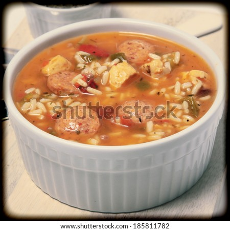 Bowl of Cajun Spicy Chicken and Sausage Gumbo Soup at Table - stock photo