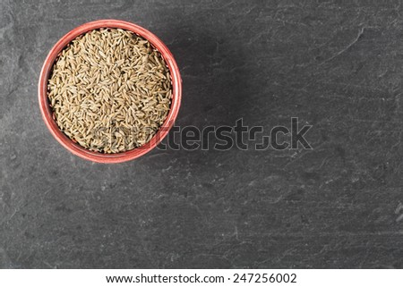 Bowl of caraway seeds on stone surface with copy space. - stock photo