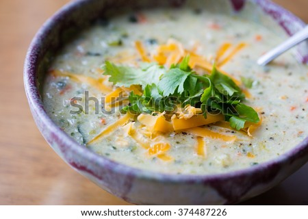 Bowl of Cauliflower Chowder with grated cheddar cheese and cilantro garnish - stock photo