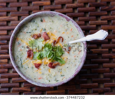 Bowl of cauliflower soup with grated cheddar cheese and cilantro garnish - stock photo