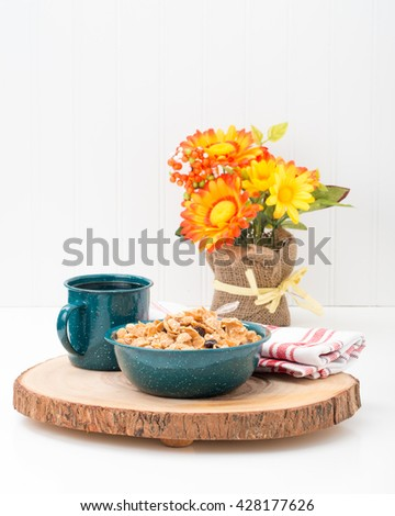 Bowl of cereal and coffee served in a tin bowl and cup. - stock photo