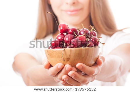 bowl of cherries in women's hands, isolated on white background - stock photo
