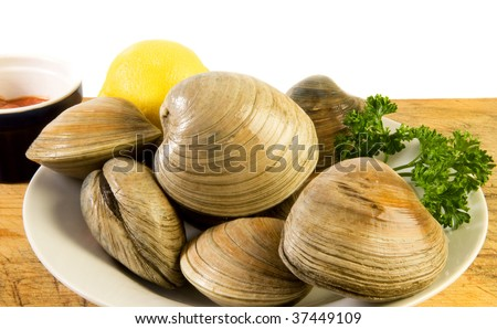 Bowl of cherrystones (quahogs, or hard-shell clams) with lemon, parsley and cocktail sauce on old cutting board - stock photo