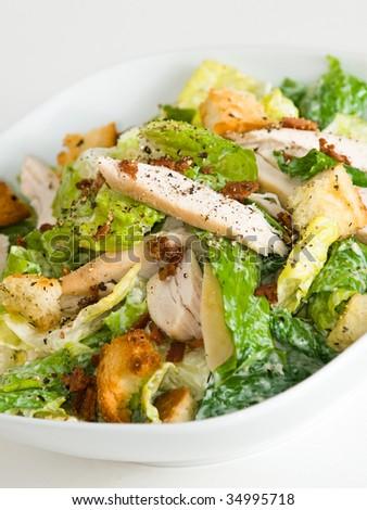 Bowl of chicken Caesar salad, on white - stock photo