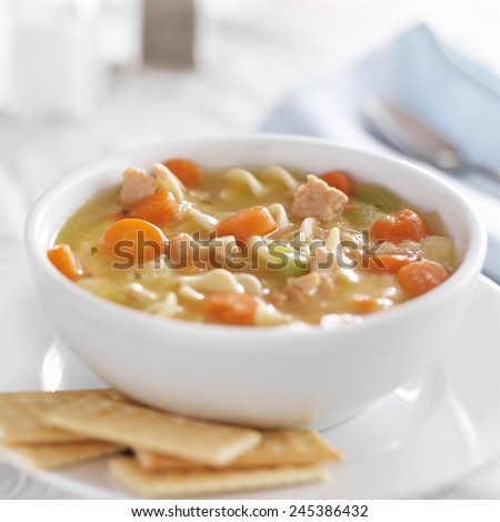 bowl of chicken noodle soup on white table cloth