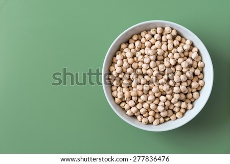 Bowl of chickpeas on green background, top view - stock photo