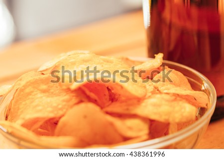 bowl of chips with brown beer bottle on blurred background. - stock photo