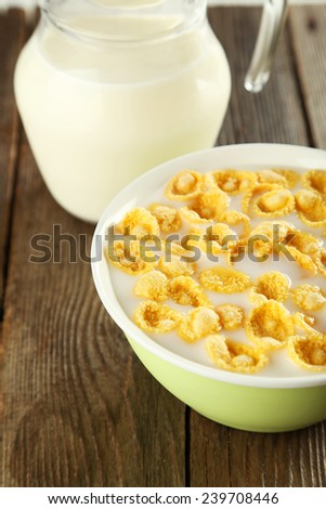 Bowl of cornflakes with milk on brown wooden background - stock photo