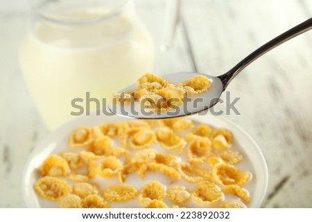 Bowl of cornflakes with milk on white wooden background - stock photo
