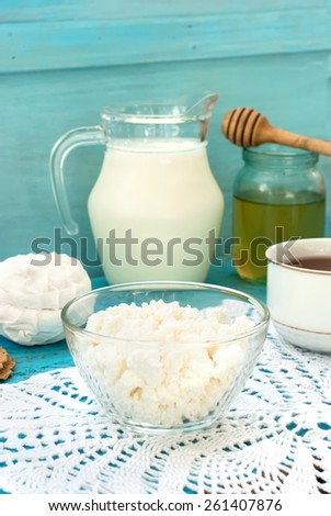 bowl of cottage cheese, a cup of tea and a pitcher of milk on a blue background - stock photo