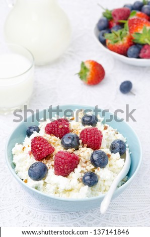 bowl of cottage cheese with berries, honey and nuts, fresh berries and milk for breakfast, vertical close-up