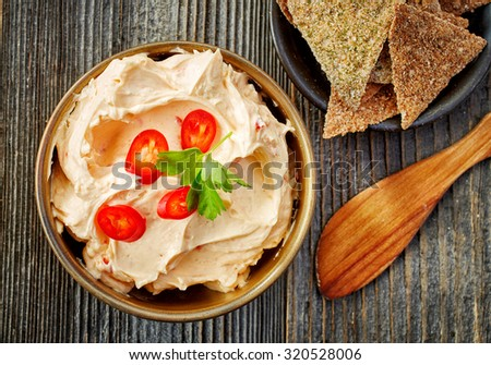 bowl of cream cheese with chili and paprika, dip sauce on wooden table, top view - stock photo