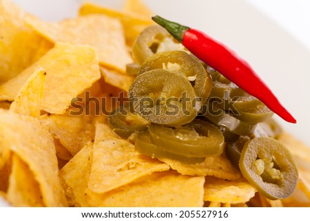 Bowl of crisp golden corn nachos with cheese sauce or dip and olives served as a starter or appetizer to a meal