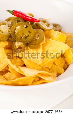 Bowl of crisp golden corn nachos with cheese sauce or dip and olives served as a starter or appetizer to a meal - stock photo