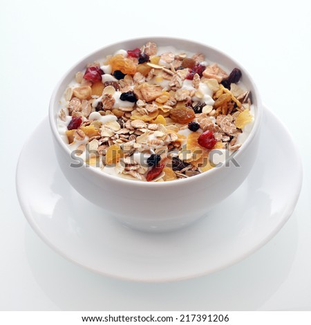 Bowl of delicious breakfast muesli with oat and wheat flakes mixed with dried fruit and nuts served in a white ceramic bowl for a healthy nutritious meal - stock photo