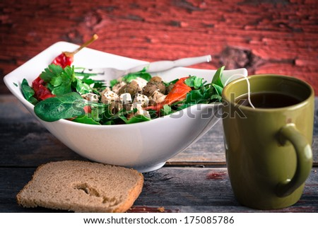 Bowl of delicious fresh baby spinach, tomato and feta salad with a mug of hot tea and a slice of bread served for lunch on a rustic wooden background with peeling paint - stock photo
