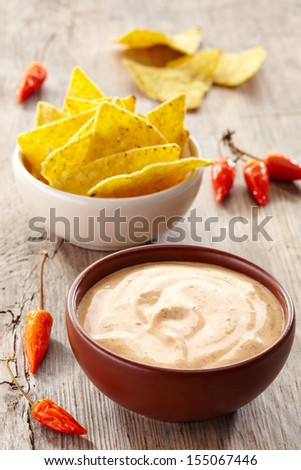 Bowl of dip and bowl of nachos on wooden background - stock photo