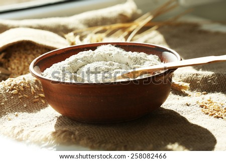 Bowl of flour with wooden spoon on burlap cloth background - stock photo