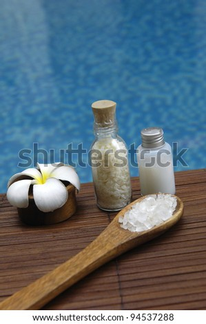 Bowl of frangipani and herbal salt in spoon and massage oil on mat in the swimming pool - stock photo