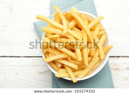 bowl of french fries on white wooden surface - stock photo