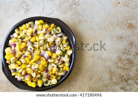 Bowl of fresh grilled corn salsa on stone surface with copy space and viewed from above.