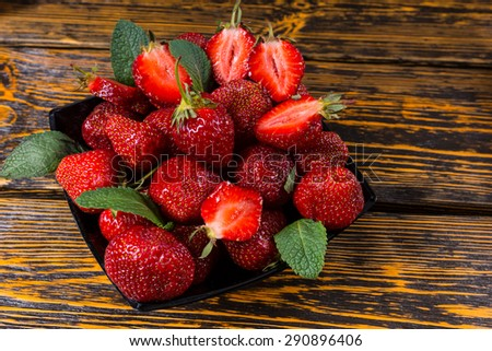 Bowl of fresh juicy ripe strawberries, halved and whole, flavored with fresh mint leaves for a delicious summer dessert viewed overhead on a rustic wooden table - stock photo