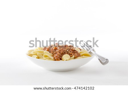 bowl of fresh pasta noodle and bolognese meat and tomato sauce in homestyle meal on bright background